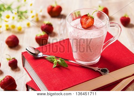 Strawberry mousse in a transparent mug on a light background with books, strawberries and chamomile flowers