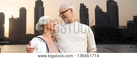 family, age, tourism, travel and people concept - happy senior couple over dubai city street background
