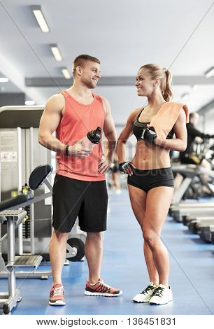 sport, fitness, lifestyle and people concept - smiling man and woman with protein shake bottle and towel talking in gym