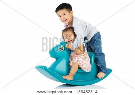 smiling asian kids playing with Toy horse