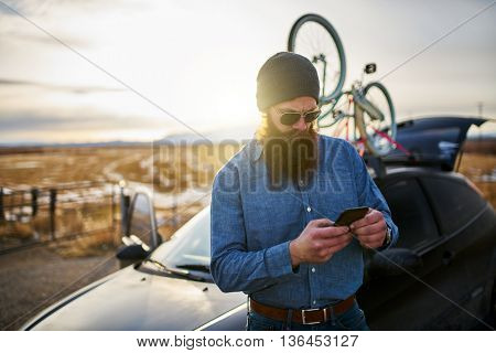 traveling bearded guy with bikes on his car using smart phone to look up directions