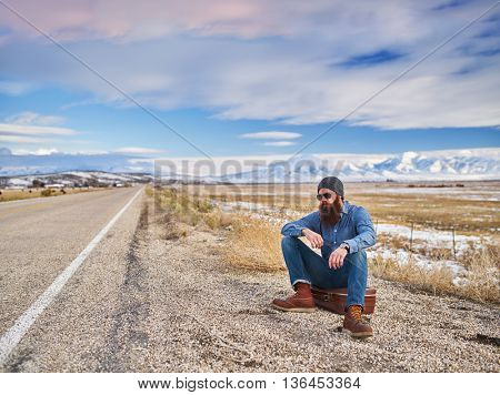 bearded traveler waiting along side road in Nevada