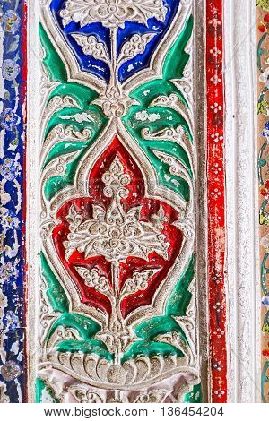 BUKHARA UZBEKISTAN - APRIL 29 2015: The close-up of the tracery fretwork on ganch painted in different colors in interior of Sitorai Mokhi-Khosa Palace on April 29 in Bukhara.