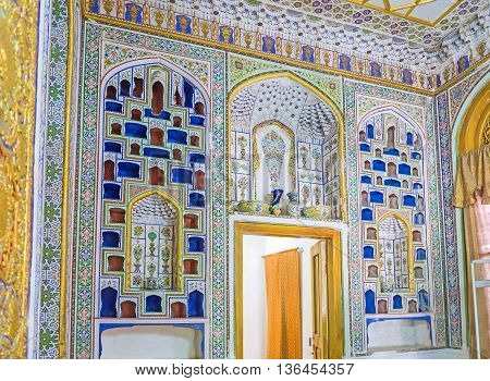 BUKHARA UZBEKISTAN - APRIL 29 2015: The wall decorated with the colorful shelves for the porcelain presented to Emir of Bukhara Museum of Costume of Sitorai Mokhi-Khosa Complex on April 29 in Bukhara.