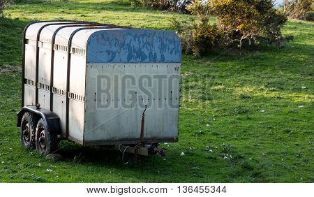 Old livestock trailer abandoned in a field