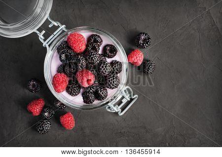 Yogurt With Black And Red Raspberry In Glass Jar