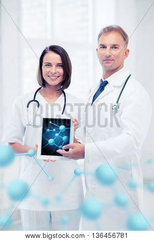 healthcare, hospital, research, science and medical concept - two doctors showing tablet pc with molecules