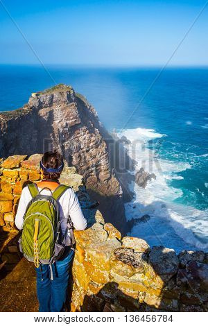 Elderly woman with a backpack standing on cliff's edge and looking into the distance. Cape of Good Hope, South Africa