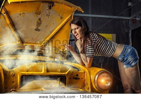 Woman mechanic in sexy shirts is pointing on a steam leak in the radiator of an old car.