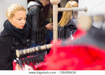 Woman shopping clothes. Shopper looking at clothing indoors in store. Beautiful blonde caucasian female model wearing casual winter clothing and black scarf.