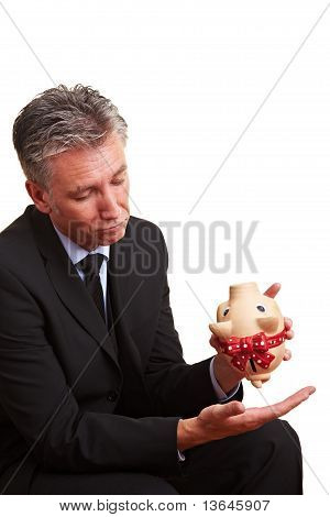 Elderly Manager With Empty Piggy Bank