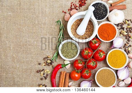spices in bowls hot peppers tomatoes and other cooking ingredients
