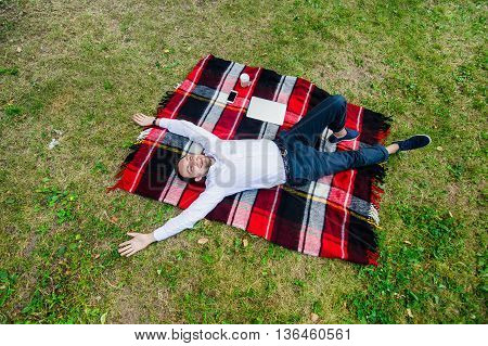 Happy young man with laptop relaxing on the grass, view from the top.