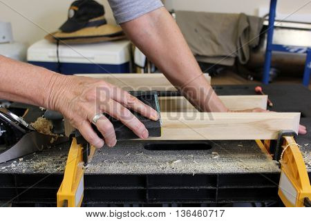 Close up of Older Woman sanding timber 3