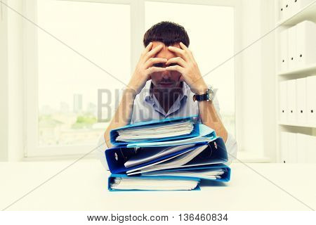 business, people, deadline, stress and paperwork concept - sad businessman with stack of folders at office
