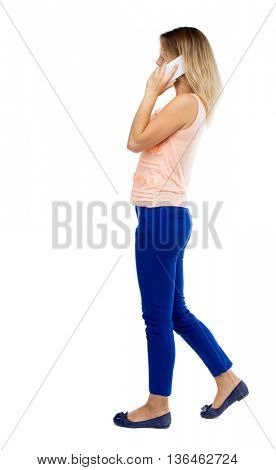 side view of a woman walking with a mobile phone. back view ofgirl in motion.  backside view of person.  Isolated over white background. Blonde in blue trousers side is talking on the white phone.