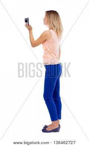 back view of standing young beautiful  woman  and using a mobile phone. girl  watching. Rear view people collection.  backside view person. Blonde in blue pants with one hand removes a compact camera
