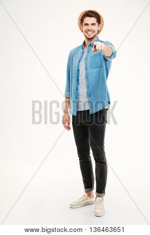 Full length portrait of a young casual man pointing finger at camera isolated on a white background