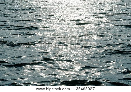 Texture of rippled sun-dappled river water reflecting sunrays at sunset making shiny sun dogs toned blue