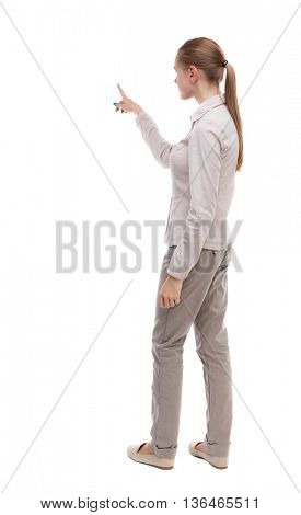 Back view of  pointing woman. beautiful girl. Rear view people collection.  backside view of person.  Isolated over white background. A girl in a white jacket presses the button with your left hand.