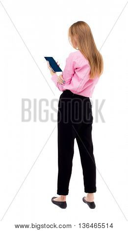 back view of standing young beautiful  girl with tablet computer in the hands of. girl  watching.  The girl office worker in black pants holding plate vertically and read from it.