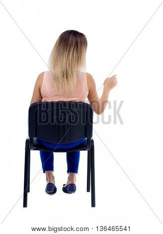 back view of young beautiful  woman sitting on chair and pointing. Rear view people collection.  backside view of person. girl is sitting on an office chair and presses his finger.