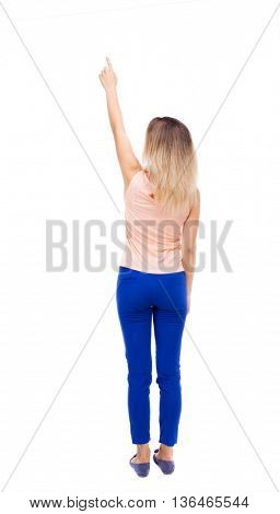 Back view of  pointing woman. beautiful girl. Rear view people collection.  backside view of person.  Isolated over white background. blonde in blue pants with his right hand is pointing up.