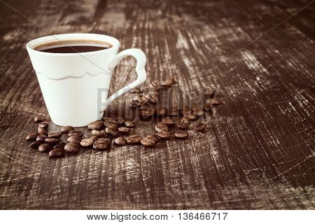 Coffee cup with roasted coffee beans on wooden background.