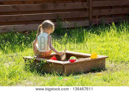 Little Girl Sitting Back Playing In Sandbox