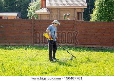 Man Mows The Grass With String Trimmer