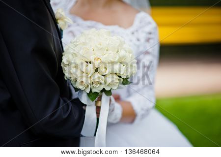 Wedding Bouquet Of White Rose In Hands Of Newlywed