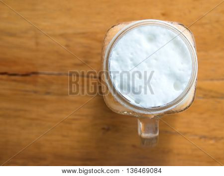 Milk tea with ice in Glass handle on wooden tableTop view focus.Milk glass top.