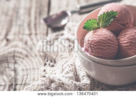 Raspberry ice cream in white bowl, rustic wood background, copy space, toned