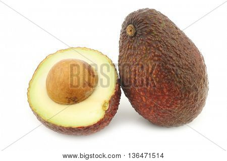 Eat ripe avocado and a cut one on a white background