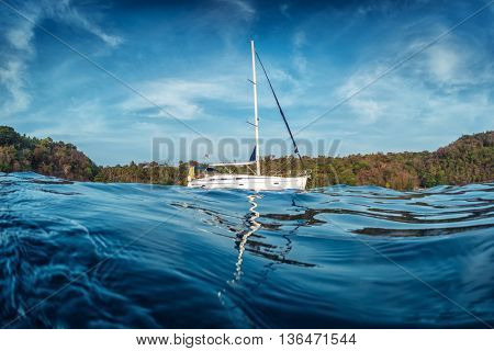 Sailing boats anchored in a sea with tropical island on the background. Andaman Sea, Thailand