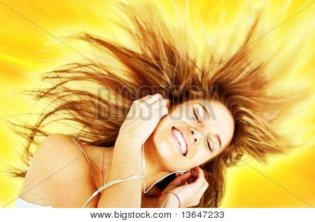 Joyful woman listening to music with eyes closed isolated over a yellow background