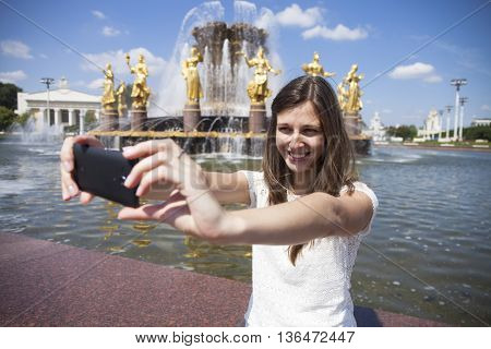 Beautiful, smiling brunette woman take a picture of herself with a smartphone. selfie, summer outdoors
