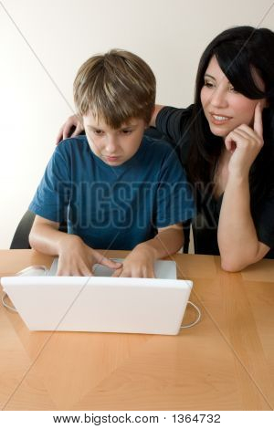 Child Using Laptop While Adult Supervises
