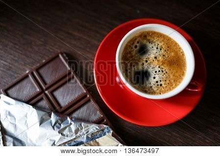 Cup Of Strong Coffee With Chocolate Bar In Foil