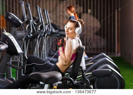 Young Woman Doing Exercises On Bicycle In Gym