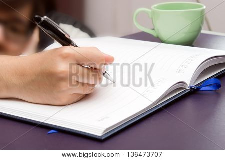 Write activity (A girl hand holds a pen and write on a book) in the morning time