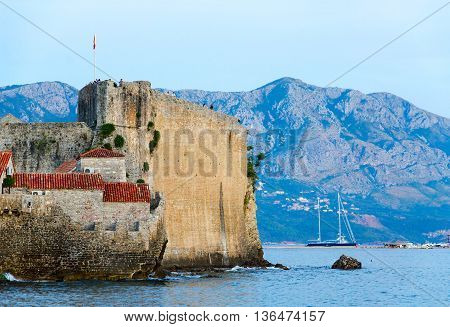 BUDVA MONTENEGRO - SEPTEMBER 15 2015: Unidentified people are admiring evening view from walls of Citadel of Old Town of Budva Montenegro