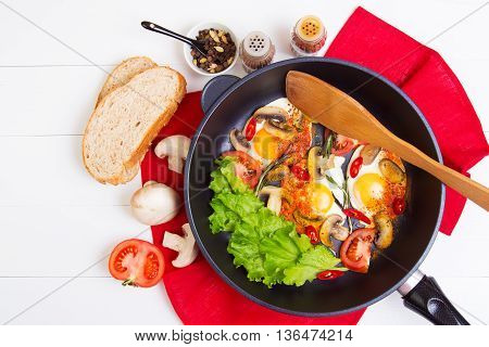 Fried eggs in pan with tomato bread pepper and mushrooms on wooden background