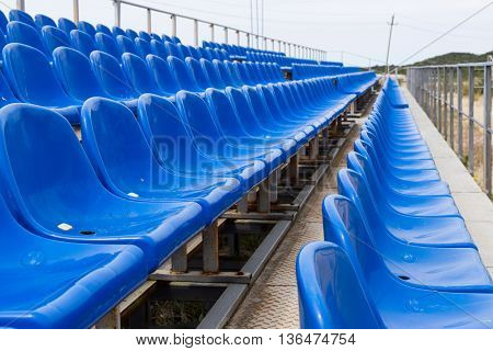 Empty plastic blue chairs at stadium in a row.