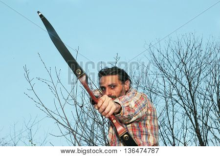 man drawing a recurve Bow aiming at camera