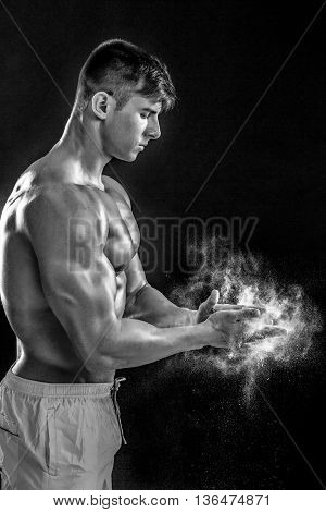 young muscular man preparing to hand lifting heavy weight. White talcum dynamically scatters in different directions.. Black and white. stands sideways