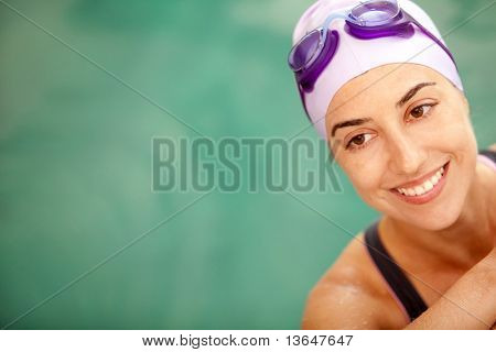 Happy female swimmer wearing a hat and goggles
