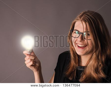 Cheerful female student with a glowing light bulb great idea concept
