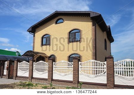 Two-storeyed yellow brick cottage with white concrete fence sunny day
