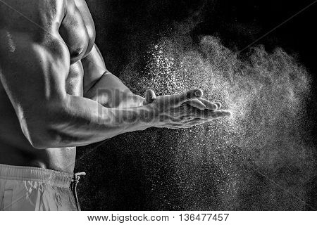 young muscular man preparing to hand lifting heavy weight. White talcum dynamically scatters in different directions. Black and white. stands sideways. Close-up